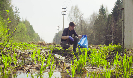 The woman ecologist collecting garbage