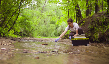 Woman ecologist taking samples of water from the creek