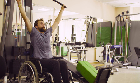 Disabled man in wheelchair doing hand exercises Imagens