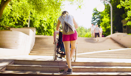 Behinderter Mann im Rollstuhl bewegt sich die Stufen hinunter Standard-Bild