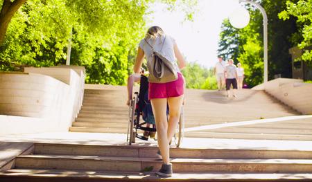 L'homme handicapé en fauteuil roulant descend les marches Banque d'images