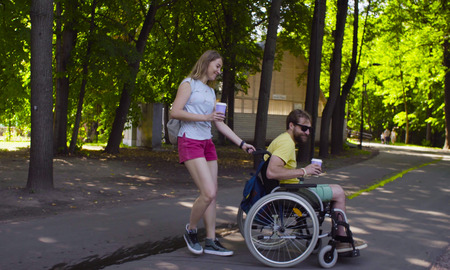 Young disable man in a wheelchair walking in the park with his wife