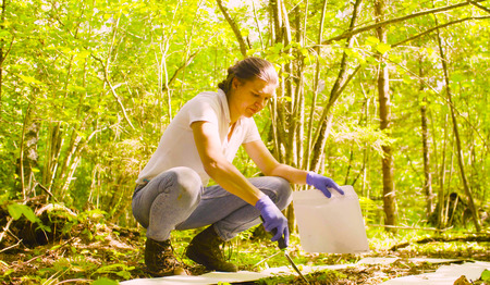 Woman getting sampels of the soil in the forest.