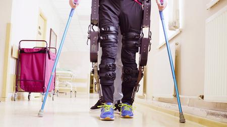 Legs of invalid in robotic exoskeleton walking through the corridor Imagens
