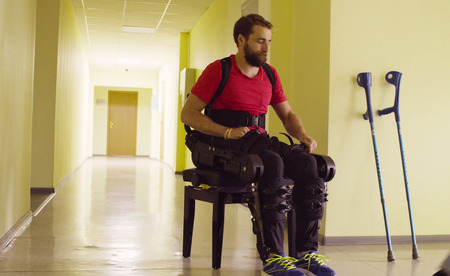Disable man in the robotic exoskeleton sitting on the bench Zdjęcie Seryjne