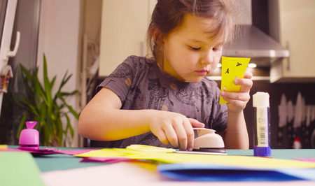Little girl cutting birds from yellow paper