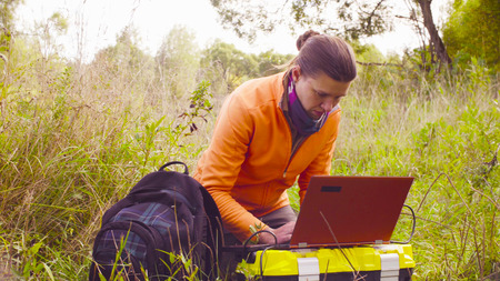 Woman scientist ecologist working on a laptop outdoors