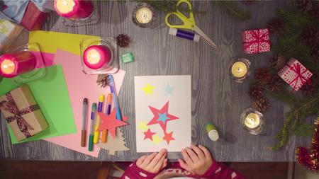 Children handicraft. Little girl glues New Year card Standard-Bild