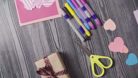 Greeting card, gift and scissors on the table