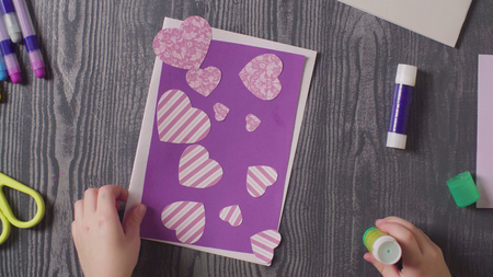 Girls hands glueing a card. Mothers Day