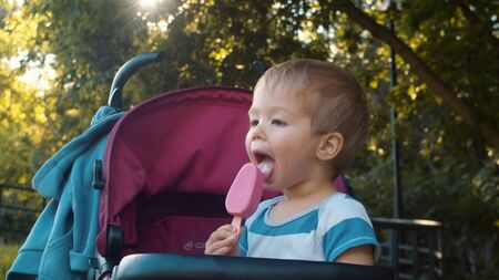 Happy small boy sitting in a stroller and eating ice cream