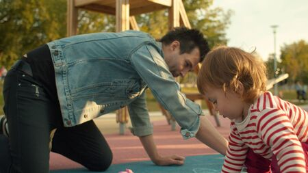 Young man draws with chalks on the playground. Small girl sitting neaby