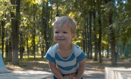 Shy and smiling charming baby boy. Kid in the park. Childhood concept.