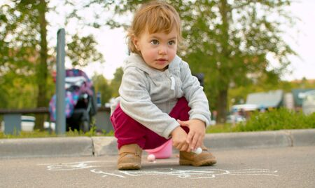 Small cute girl drawing on asphalt in the park