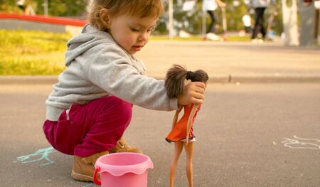 Funny baby playing with a doll against skate park