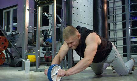 Man athlete doing exercise with ab wheel in gym. Fitness, sport, exercising, training and lifestyle concept.