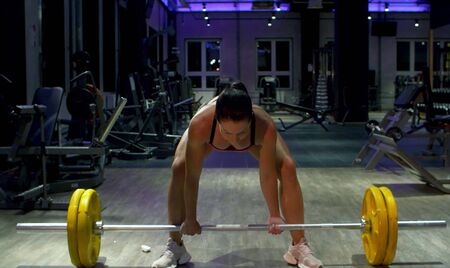 Woman bodybuilder lifting barbell. Athlete in the gym. Fitness, sport, and training concept