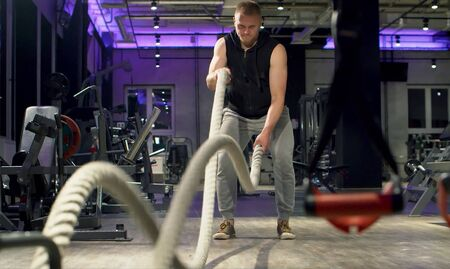 Man bodybuilder doing exercise using battle ropes in gym. Fitness, sport, exercising, training and lifestyle concept. 版權商用圖片 - 128403247