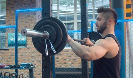 The male athlete before lifting the barbell. Bodybuilder in the gym