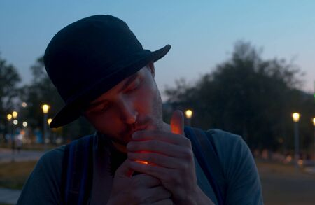 Portrait of a young man lights a cigarette on the night city park background