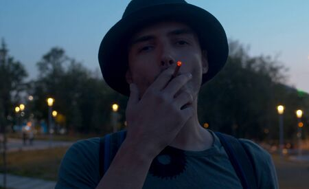 Portrait of a young man smoking a cigarette on the night city park background