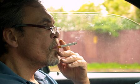 Close up portrait of handsome senior man driving a car and smoking. Shooting inside the car 版權商用圖片