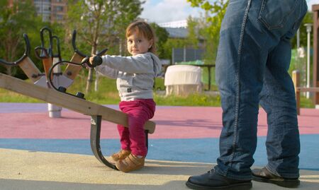 Small cheerful baby girl on the swing in the park