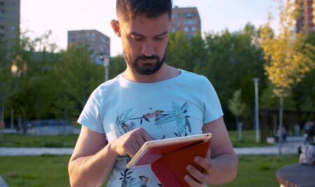 Man scrolling the tablet in the park