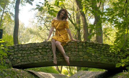 Rural scene. Young woman in a beautiful yellow dress posing on a stone bridge