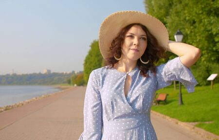 Cinematic woman in a long blue retro dress and a straw hat walking on the embankment along the river