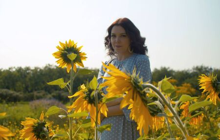 Portrait of a young woman in a garden among sunflowers