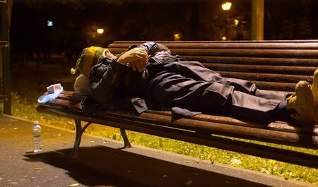 A homeless man sleeping on a bench in a park Stock Photo