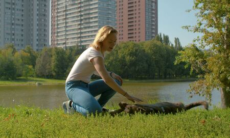 Young attractive lady with her dog in the park at summer. Woman playing with the dog. Dog lying on the grass and having fun