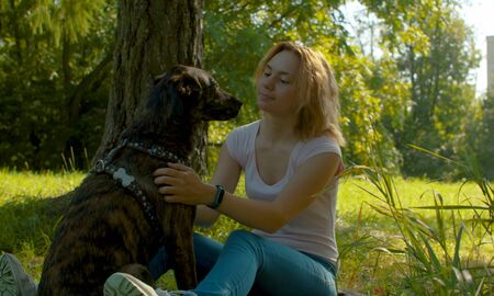 Two best friends - attractive young lady and her dog in the park.