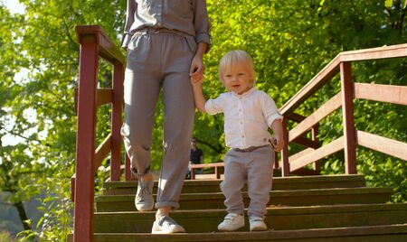 Baby boy walking on the bridge in the park. Mom holding his hand. Outdoors 版權商用圖片