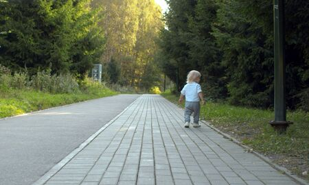 Toddler walking along the road, mom running behind. Mother and her son on the stroll in the park. Family.