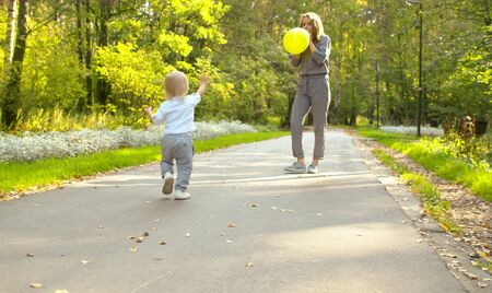 Young attractive mother and funny baby in the park. Mom inflates a balloon, her little son goes to her. Family, Mother's Day
