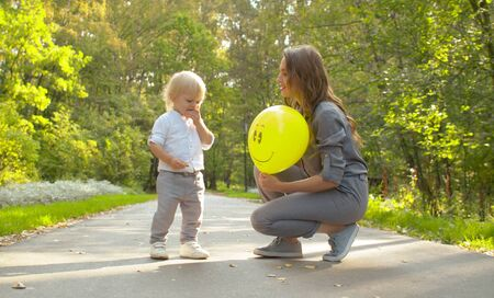 Young attractive mother and funny baby in the park. Mom giving a balloon to her little son. Family, Mothers Day.