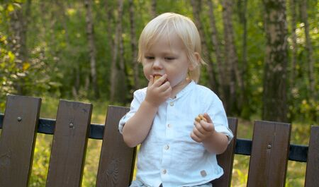 Close up portrait shot of funny toddler standing on the bench and eating cookies