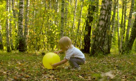 Small funny kid with yellow baloon playing among the trees.