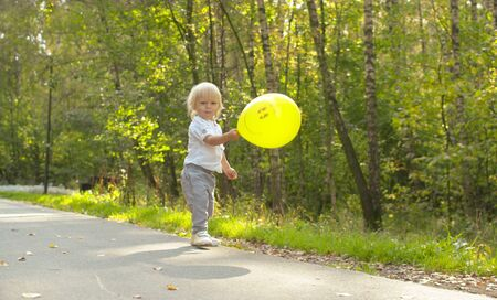 Small funny kid with yellow baloon playing on the road in the park