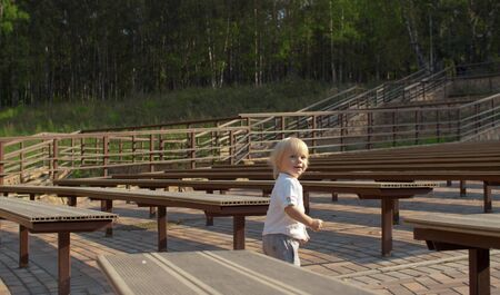 Little blond boy walking between the benches in an outdoor theater