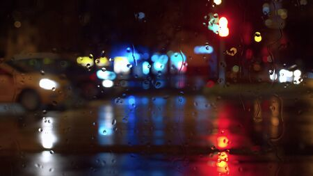 Rain water drops on window glass. Blurred night city traffic lights. City background