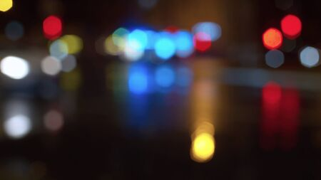 Blurred night city traffic lights. Rainy. Reflection of the colorful lights on the wet asphalt. City background