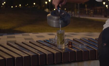 Tea ceremony in the park at night. Man pouring hot water in the transparent teapot
