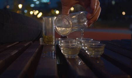 Tea ceremony in the park at night. Man pouring green tea in the transparent cups 版權商用圖片