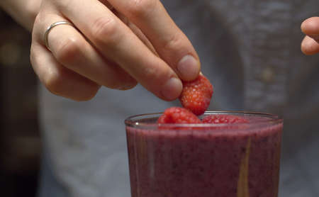 Close up glass of ready made smoothies on the table. Female hands gently decorating it with raspberries and blueberries closeup. Fresh healthy food 写真素材