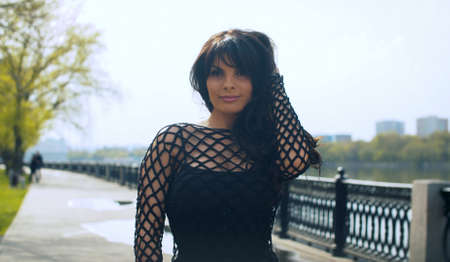 Beautiful smiling woman in black clothes on the embankment in the city park. Nice early spring day. Real people