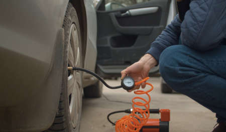 Close up of man holding a manometer in his hand while a pump inflates a car wheel. Vehicle auto maintenance Banco de Imagens