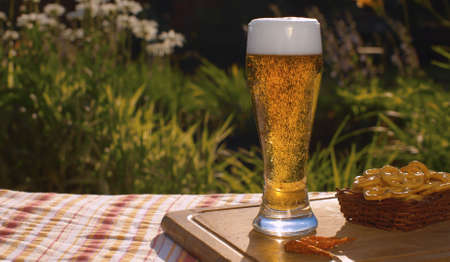 Close up glass of cold light beer on the table outdoors. Foamy sparkling gold drink on natural background in the garden